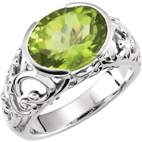 Gemstone ring set wotj oval cut peridot in 4kt white  with sculpted sides.