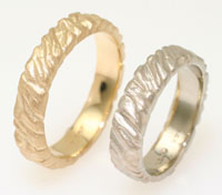 Unique wedding bands, sculpted surfaces are sandblasted white gold and yellow gold.
